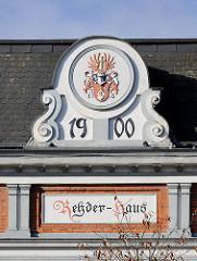 Historische Architektur in Bad Segeberg - Fassade vom Rehder-Haus, erbaut 1910; Bauschmuck Wappen, Jahreszahl und Name.