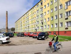 Plattenbau - mehrstöckiger Wohnblock mit grüner, gelber Fassade Darłowo / Rügenwalde, Polen. Parkende Autos auf einem Sandplatz, Alter Fabrikschornstein - Fahrradfahrerin.