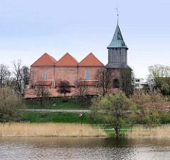 Blick über den Fluss Nogat in Malbork / Marienburg, Polen zur Pfarrkirche St. Johannis - gotischer  Backsteinbau - Kirchturm mit Glockengeschoss aus Holz.