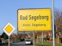 """Gelbes Ortschild """"Bad Segeberg"""" - """"Kreis Segeberg""""; schwarze Schrift, gelber Grund."""