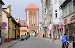 Geschäftsstrasse und historisches Steintor in Darłowo / Rügenwalde, Polen.