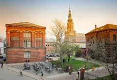 Universitätsgebäude - Backsteinarchitektur in der Hansestadt Greifswald; im Hintergrund der Turm vom St. Nicolai Dom.