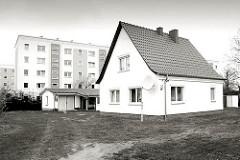 Einzelhaus - Baustil der 1950er Jahre, Spitzdach - Garage; im Hintergrund mehrstöckige Wohnhäuser - Schwarz weiss Fotografie.