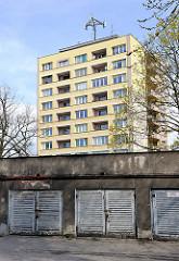 Hochhaus mit gelber Fassade, Wohnhaus - alte Garagentore aus Holz im Vordergrund / alt + neu, Architektur.