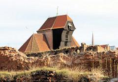 Mit Gras überwucherte Mauerreste auf der Speicherinsel Danzigs - dahinter  das Krantor / Stadttor an der Mottlau.