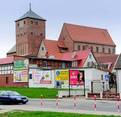 Schloss der pommerschen Herzöge, Rügenwalder Schloss an der Wipper in Darłowo / Rügenwalde, Polen. Bunte Werbeplakate an Hauswänden an der Strasse.