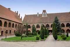 Gotische Backsteinarchitektur in Dobre Miasto, Polen - Stiftsgebäude, Innenhof mit Grünanlage.