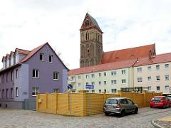 Etagenhaus mit violetter Fassade - mehrstöckige Wohnblocks - Marienkirche; Backsteingotik aus dem 13. Jahrhundert.