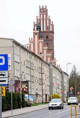 Backsteinturm  / Ziegelfassade der  Kollegiatskirche in Dobre Miasto, Polen; Neubau eines mehrstöckigen Wohngebäudes; Strassenverkehr - neu + alt.