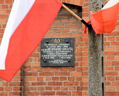 Gedenktafel BERNARD SYCHTA in Pelplin, Polen - polnische Flaggen, weiss-rot. Bernard Sychta war Pfarrer an der Kathedrale von Pelplin und schrieb ein Kompendium über die Kultur der Kaschuben.