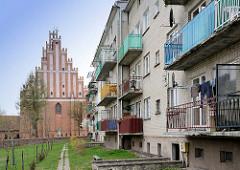 Backsteinfassade der  Kollegiatskirche in Dobre Miasto, Polen; Balkons eines Neubaus, mehrstöckiges Wohngebäude - neu + alt.