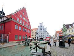 Alter Fischmarkt mit Fischerbrunnen in Greifswald. Lks. das historische gotisch barocke Rathaus aus dem 13. Jahrhundert.