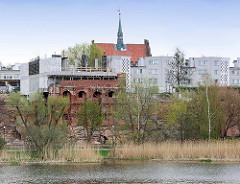 Blick über den Fluss Nogat in Malbork / Marienburg, Polen zur Befestigungsanlage der Stadt, dahinter Neubauten und das histoirsche Rathaus der Stadt.