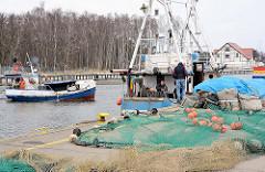 Fischereihafen Łeba, Polen - Netze sind am Kai zum Trocknen ausgebreitet - ein Fischerboot fährt in den Hafen ein.