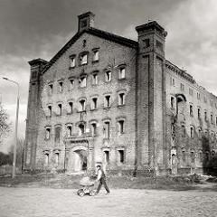 Verlassene Industriearchitektur - Industrieruine; Mann mit Kinderwagen - Schwarz-Weiss Fotografie von Architektur in Danzig / Gedansk.