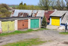 Garagen mit farbigen Holztoren - Haus mit Wellblechdach + Garageneinfahrt; Bilder aus Trzebiatow / Treptow an der Rega.