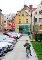Strassenszene in Lidzbark Warmiński / Heilsberg - parkende Autos, spielendes Kind mit Roller.