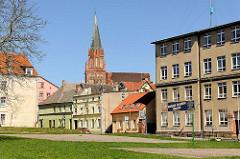 Wohnhäuser, einstöckig - mehrstöckig - schlichte Architektur; hinter den Häusern die Backsteinarchitketur der Marienkirche  Trzebiatow / Treptow an der Rega.
