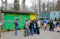 Besucher auf dem Gelände der Wolfsschanze  /  Wilczy Szaniec stehen vor einer Informationstafel - Lageplan.