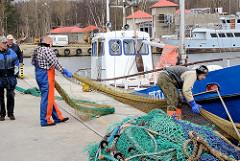 Fischereihafen an der Ostsee in Łeba, Polen - Fischer arbeiten an den Netzen.