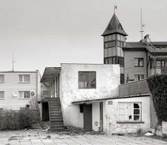 Architektur aus dem polnischen Badeort Leba - neugebautes Hotel, Restaurant mit Giebelturm; verfallenes einfaches Wohngebäude mit zerbrochenen Fensterscheiben.