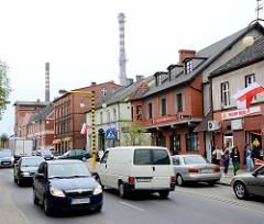 Autoverkehr - Durchgangsstrasse in Pelplin, Polen - Gebäude unterschiedlicher Architektur; Geschäfte.