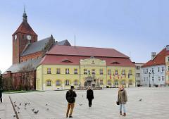 Marktplatz von Darłowo / Rügenwalde, Polen; Rathaus  und gotische Marienkirche - Touristen fotografieren sich auf dem Platz.