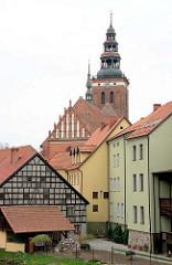 Die Kirche St. Peter und Paul in Lidzbark Warmiński / Heilsberg überragt Wohnhäuser, Wohnblocks und Fachwerkhaus.
