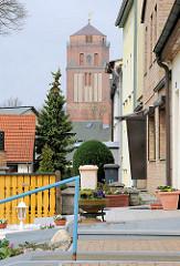 Hauseingänge von Wohnhäusern; im Hintergrund der Kirchturm der Petrikirche; zwischen 1280 und 1350 im gotischen Stil erbaut.