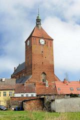 gotischen Marienkirche in Darłowo / Rügenwalde, Polen. Die dreischiffige Basilika entstand im 14. Jahrhundert. Einstöckige Wohnhäuser und Schuppen im Vordergrund.
