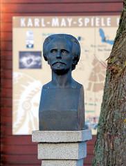 Bronzebüste von Karl May - im Hintergrund ein Hinweisschild der Karl-May-Spiele auf dem Kalkberg in Bad Segeberg.