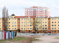 Wohnblocks, Etagenhäuser - Hochhaus mit rosa Fassade; Brachgebiet.