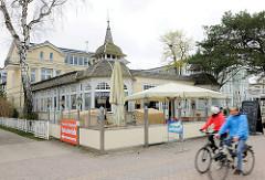 Strandpromenade Gemeinde Dreikaiserbäder, Heringsdorf - Usedom /  - Restaurant, Café im Baustil der Bäderarchitektur; FahrradfahrerIn mit Regenjacken.