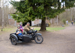 Gegen Entgelt werden Besucher in einem Motorrad / Beiwagen, Motorradgespann über das Gelände der Wolfsschanze  /  Wilczy Szaniec gefahren.