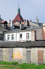 Schuppen mit Holztüren im Hinterhof - Dächer von Darłowo / Rügenwalde, Polen. Kirchturm mit Kupferkuppel von der gotischen Marienkirche.