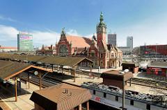 Blick über die Bahngleise - Bahnsteig; Bahnhofsgebäude des Hauptbahnhofs von Danzig, Rückseite - historisierende Architekturform; Backsteingebäude im Stil der Neurenaissance.
