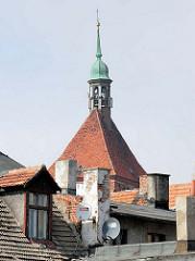 Schornsteine und Dachfenster - Kirchturmspitze mit Kupferkuppel der Marienkirche in Darłowo / Rügenwalde, Polen.