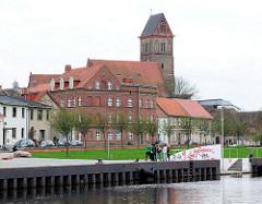 Blick über das Hafenbecken in Anklam - mehrstöckige Wohngebäude und der Kirchturm der Marienkirche - die dreischiffige Hallenkriche der Backsteingotik stammt aus dem 13. Jahrhundert.