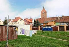 Wiese hinter Wohnhäuser - Wäsche hängt zum Trocknen auf der Leine in der Sonne - Kirchturm der Marienkirche in Darłowo / Rügenwalde, Polen.