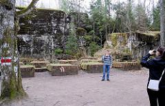 Touristen auf dem Gelände der Wolfsschanze  /  Wilczy Szaniec - sie besichtigen einen zerstörten Bunker und machen ein Andenkenfoto.