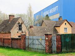 Grundstück mit Einzelhaus - Ziegelmauer mit Holztor - Werftgebäude der Peene-Werft.