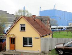 Einzelhaus in Wolgast - ein Zug fährt am Grundstück entlang; im Hintergrund ein Werftgebäude der Peene-Werft.