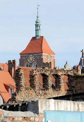 Mauerreste - Fensterhöhlen, Backstein / Ziegelstein - Ruine auf der Speicherinsel von Danzig - im Hintergrund Backstein-Kirchturm mit Ziegeldach und Kupferspitze.