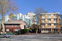Historische Architektur, altes Wohnhaus mit Holzfassade - moderne Wohnblocks mit farbiger Fassade, Balkons - Architekturfotos aus Międzyzdroje / Misdroy auf der Insel Wolin.