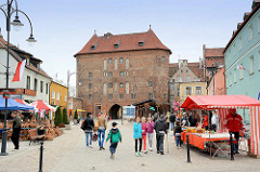 Geschäftsstrasse in Lidzbark Warmiński / Heilsberg - Verkaufsstände in der Fussgängerzone - im Hintergrund das Hohe Tor, Teil der alten Befestigungsanlage der Stadt.
