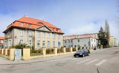 Historisches Verwaltungsgebäude - Gründerzeitvilla in Darłowo / Rügenwalde, Polen. Im Hintergrund mehrere Wohnblocks, Neubauten - neu + alt.