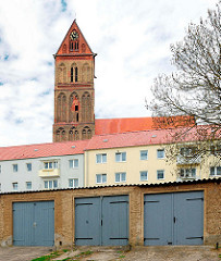 Wohnhäuser und Garagentore in Anklam - Kirchturm der Marienkirche aus dem 13. Jahrhundert.