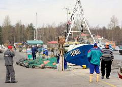 Fischereihafen an der Ostsee in Łeba, Polen - Netze liegen am Kai; Fischer + Fischkutter.