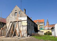 Altes baufälliges Wohnhaus mit Balken abgestützt - im Hintergrund Neubauten und die Marienkirche in Trzebiatow / Treptow an der Rega.
