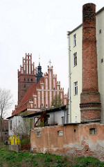 Blick auf die Kollegiatskirche in Dobre Miasta / Guttstadt, Polen - dreischiffige gotische Hallenkirche, errichtet 1357 - 1389 - Backsteinarchitektur. Wohngebäude - Ziegelschornstein.